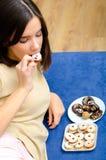 Adolescente hermoso que come las galletas del chocolate en casa Fotos de archivo libres de regalías