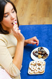 Adolescente hermoso que come las galletas del chocolate en casa en cama Imagen de archivo