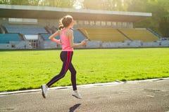 Adolescente hermoso que corre en estadio Imagen de archivo libre de regalías