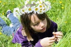 Adolescente hermoso que cuenta los pétalos en hierba Fotos de archivo