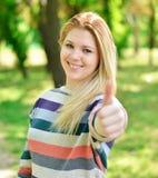 Adolescente hermoso que detiene los pulgares al aire libre Fotografía de archivo libre de regalías
