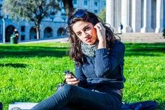Adolescente hermoso que disfruta de música en el smartphone que mira al fotógrafo Foto de archivo libre de regalías
