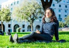 Adolescente hermoso que disfruta de música en el smartphone, relajándose Imagenes de archivo