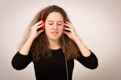 Adolescente hermoso que disfruta de música en los auriculares Foto de archivo