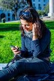 Adolescente hermoso que disfruta de música en smartphone Fotos de archivo libres de regalías