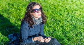 Adolescente hermoso que disfruta de música en smartphone y que disfruta del día soleado Fotografía de archivo libre de regalías