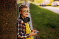 Adolescente hermoso que escucha la música y que usa el teléfono Imagen de archivo libre de regalías