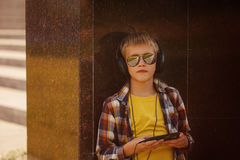 Adolescente hermoso que escucha la música y que usa el teléfono Imagenes de archivo