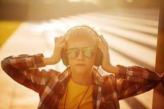 Adolescente hermoso que escucha la música y que usa el teléfono en puesta del sol Imagen de archivo libre de regalías