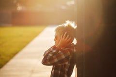 Adolescente hermoso que escucha la música y que usa el teléfono en puesta del sol Foto de archivo