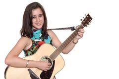Adolescente hermoso que juega un guita acústico aislado en blanco Imagen de archivo libre de regalías