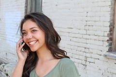 Adolescente hermoso que llama por el teléfono afuera con el espacio de la copia en el lado derecho Foto de archivo