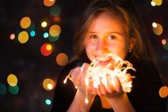 Adolescente hermoso que lleva a cabo luces festivas Fotografía de archivo