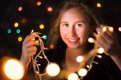 Adolescente hermoso que lleva a cabo luces festivas imagen de archivo libre de regalías