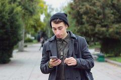 Adolescente hermoso que manda un SMS en un teléfono móvil Fotografía de archivo