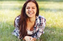 Adolescente hermoso que miente en campo de la hierba verde Fotografía de archivo libre de regalías