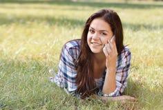 Adolescente hermoso que miente en campo de la hierba verde y de la charla por el teléfono Fotos de archivo