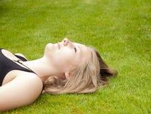 Adolescente hermoso que miente en ella detrás en la hierba Imagen de archivo