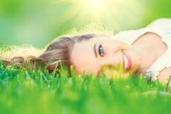 Adolescente hermoso que miente en hierba verde Fotos de archivo libres de regalías