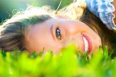 Adolescente hermoso que miente en hierba verde Foto de archivo libre de regalías