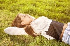 Adolescente hermoso que miente en la hierba Imagenes de archivo