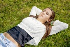 Adolescente hermoso que miente en la hierba Foto de archivo libre de regalías
