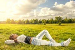 Adolescente hermoso que miente en la hierba Fotos de archivo