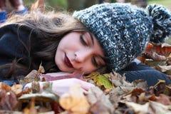 Adolescente hermoso que miente en una cama de hojas caidas Fotos de archivo