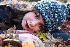 Adolescente hermoso que miente en una cama de hojas coloridas en Aut Foto de archivo libre de regalías