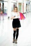 Adolescente hermoso que mira el teléfono móvil en cente de las compras Fotos de archivo
