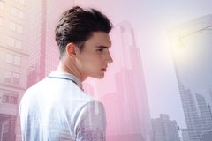 Adolescente hermoso que mira lejos contra edificios de la ciudad Imagen de archivo libre de regalías