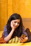 Adolescente hermoso que mira su teléfono elegante con asthonis Imagenes de archivo
