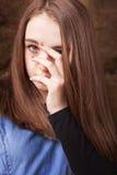 Adolescente hermoso que mira a través de sus fingeres Imagenes de archivo