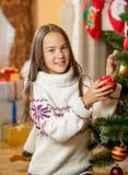 Adolescente hermoso que presenta en el árbol de navidad con la chuchería roja Imagen de archivo libre de regalías