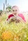 Adolescente hermoso que se acuesta en hierba en primero plano Imagenes de archivo