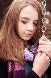 Adolescente hermoso que se aferra a una cadena de un oscilación Fotografía de archivo libre de regalías