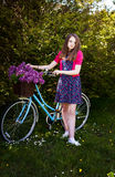 Adolescente hermoso que se coloca al lado de una bicicleta con una cesta o Imagen de archivo
