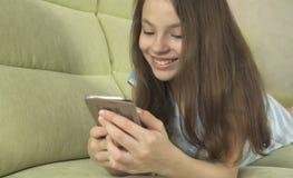 Adolescente hermoso que se divierte que comunica en smartphone Imagen de archivo