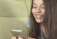 Adolescente hermoso que se divierte que comunica en smartphone Fotos de archivo