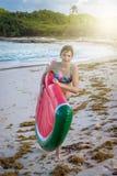 Adolescente hermoso que se divierte en la playa con un juguete inflable en el mar del Caribe Imagen de archivo