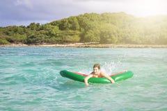 Adolescente hermoso que se divierte en la playa con un juguete inflable en el mar del Caribe Fotos de archivo