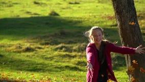 Adolescente hermoso que se divierte que juega en el bosque del otoño ella lanza las hojas amarillas caidas en el aire La muchacha almacen de metraje de vídeo