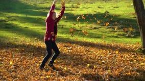 Adolescente hermoso que se divierte que juega en el bosque del otoño ella lanza las hojas amarillas caidas en el aire La muchacha metrajes