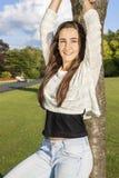 Adolescente hermoso que se inclina en un árbol Imágenes de archivo libres de regalías