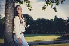 Adolescente hermoso que se inclina en un árbol Fotografía de archivo