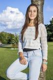 Adolescente hermoso que se inclina en un árbol Imagen de archivo
