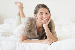 Adolescente hermoso que se relaja en cama Imagen de archivo