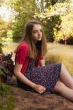 Adolescente hermoso que se sienta al lado de un río Foto de archivo