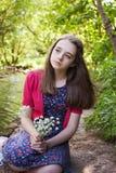 Adolescente hermoso que se sienta al lado de un río Fotografía de archivo libre de regalías