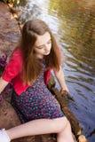 Adolescente hermoso que se sienta al lado de un río Fotografía de archivo